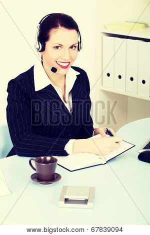 Beautiful business woman with headphones and microphone is sitting behing desk.