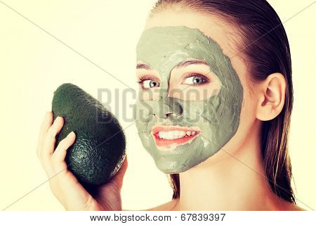 Beautiful spa woman in facial mask and avocado