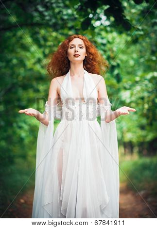 Gorgeous Red-haired Woman Wearing White Dress In A Garden