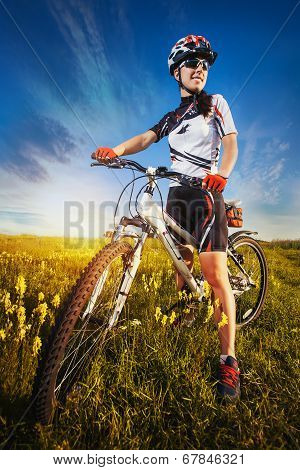 Woman is riding bicycle outside in the field