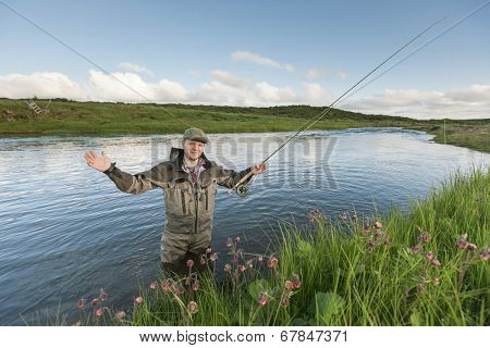 Flyfisherman showing the size of a fish that just got away