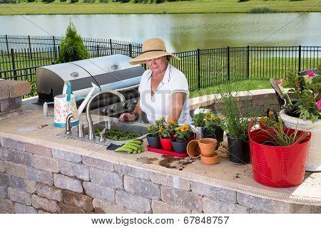 Senior Lady Working In Her Summer Kitchen