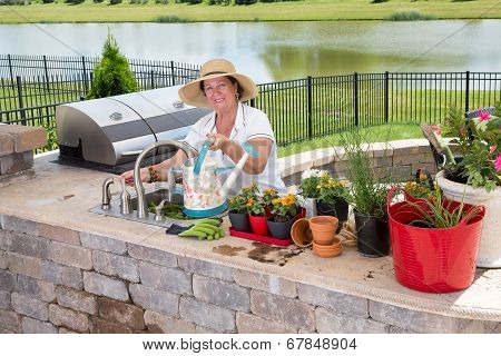 Retired Senior Woman Gardening, In A Brick Patio