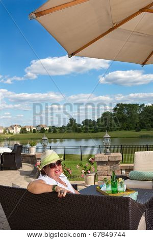 Elderly Woman Relaxing On An Outdoor Brick Patio