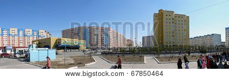 Nadym, Russia - May 17, 2008: The Panorama. Urban Landscape, Unfamiliar People Walk On The Square.