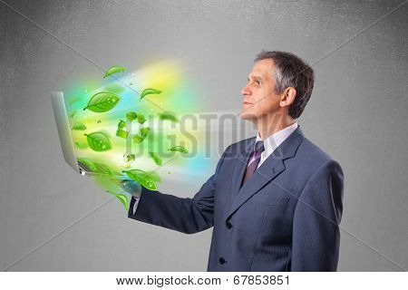 Handsome businessman holding laptop with recycle and environmental symbols
