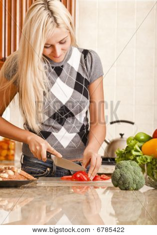 Young Woman Cutting Tomato