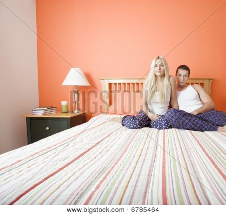 Young Couple In Pajamas Sitting On Bed