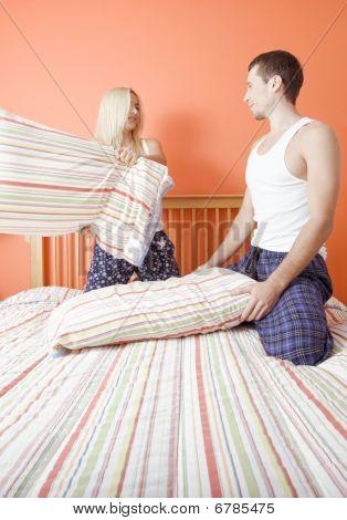 Pareja joven arrodillada sobre la cama con una pelea de almohadas