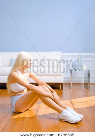 Young Woman Sitting On Wood Floor