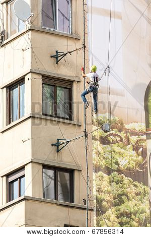 Alpinist Worker Fixing Advertising