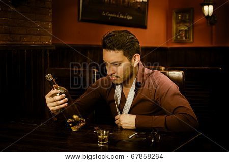 latin guy drinking shots staring at bottle