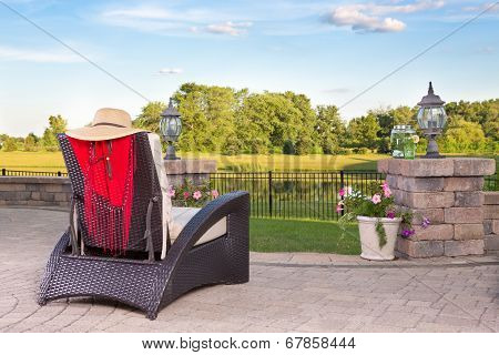 Vacant Wicker Armchair Overlooking A Tranquil Pond