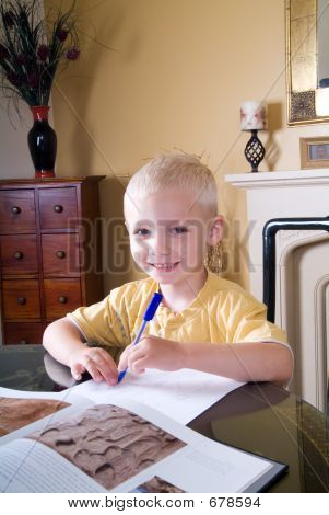 Boy Writing At Table