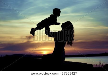 Silhouette of a young mother with her little child