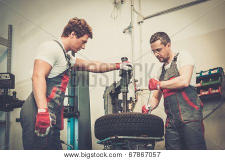 Two mechanics changing tire on a wheel in a car workshop