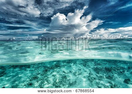 Amazing seascape, dramatic cloudy sky, coral gardens under beautiful transparent water, beauty of nature, summer time concept