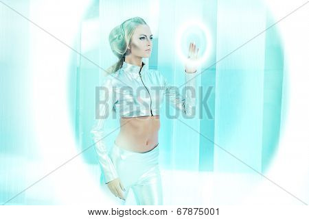 Beautiful young woman in silver latex costume with futuristic hairstyle and make-up. Touchscreen. Sci-fi style.