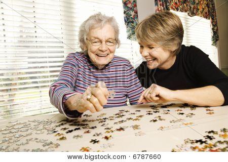 Mulher idosa e jovem mulher fazendo o quebra-cabeça