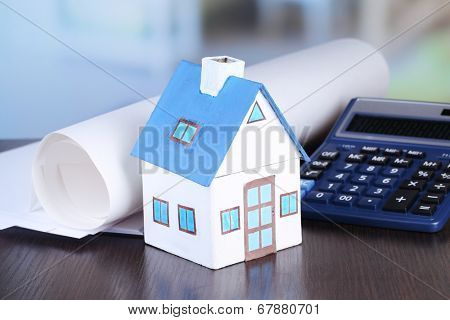 Toy house and calculator on table close-up