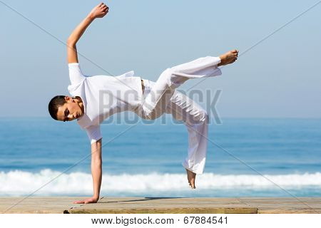 healthy young woman practicing capoeira on the beach