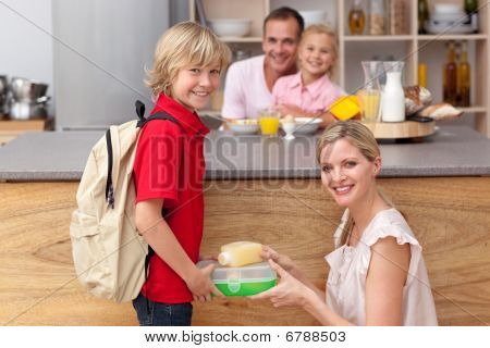 Attentive Mother Packing The School Lunch To His Son