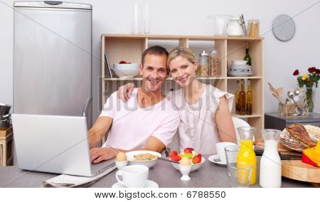 Young Couple Using A Laptop While Having Breakfast