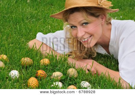 Young woman and easter eggs on the grass - Easter time