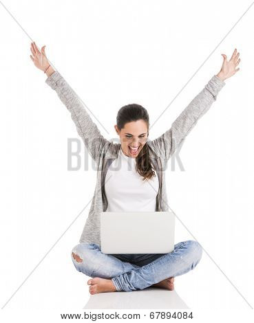 Beautiful happy woman with arms up sitting with crossed legs and working with a laptop
