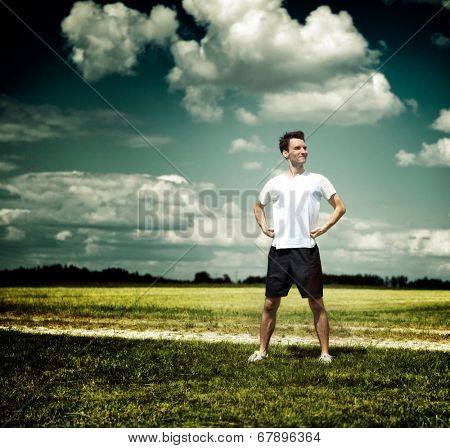 Fit handsome young male athlete pausing during his daily workout to admire the countryside standing against a dramatic sky with his hands on his hips and a pleased smile