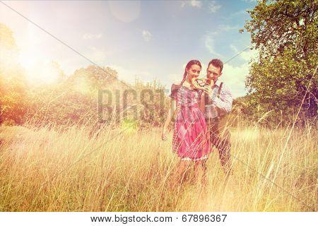 Loving couple in traditional Bavarian Dirndl and Lederhosen eat a brezel outside