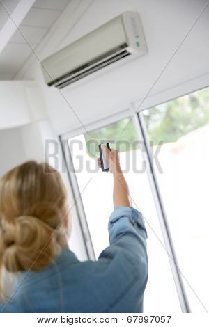 Woman controlling temperature from air conditioner