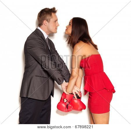 Boyfriend restraining adorable girlfriend wearing boxing gloves from fighting on white background