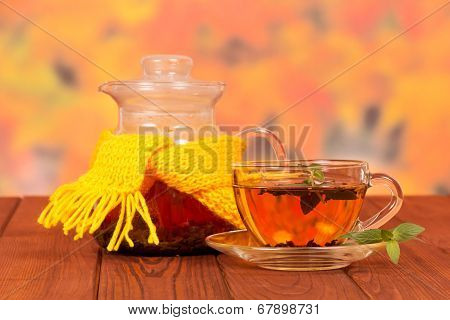 Teapot tied with yellow scarf and cup of tea