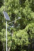 image of solar battery  - Solar battery powers an electric lamp in the park - JPG