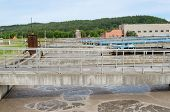 stock photo of aeration  - Modern treatment cleaning plant wastewater sewage water aeration basin bubbling and big pipes blowing oxygen - JPG