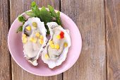 stock photo of oyster shell  - Tasty cooked oysters in shell on wooden table - JPG