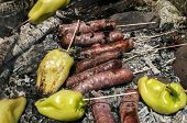 pic of ember  - Raw sausages and peppers preparing on hot fireplace wood embers during picnic in forest meadow - JPG