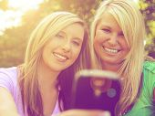 stock photo of two women taking cell phone  - two friends taking a selfie in a park while the sun is setting - JPG