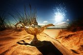 picture of genie  - Magic lamp in the desert from the story of Aladdin with Genie appearing in blue smoke concept for wishing - JPG