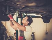 picture of suspension  - Serviceman checking suspension in a car workshop  - JPG