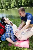 picture of tickle  - Boy tickling girl by the lake vertical - JPG