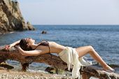 stock photo of sunbather  - Sunbather beautiful woman sunbathing on the beach with the sea in the background - JPG
