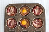 image of bacon strips  - Raw Bacon and Eggs in a muffin pan just before baking - JPG