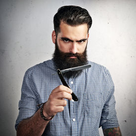 stock photo of razor  - Brutal bearded man with vintage straight razor - JPG