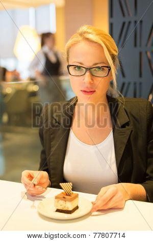Woman eating dessert in fancy restaurant.