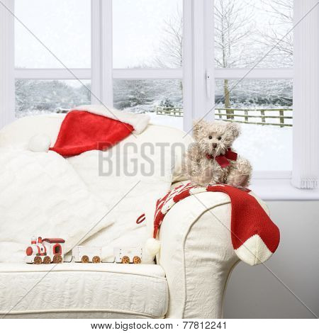 Little teddy bear Christmas stocking and train set sitting by window