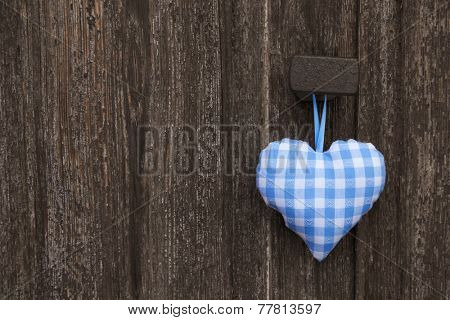 Fabric blue and white checked heart in bavarian style hanging on an old wooden background.