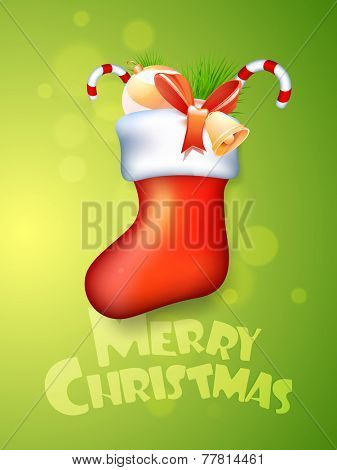 Glossy X-mas stocking with jingle bell, candy canes, decoration ball and fir tree on shiny green background for Merry Christmas celebrations.