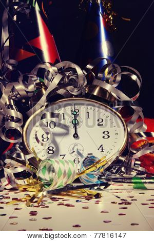 Alarm clock and decorations on table with festive background